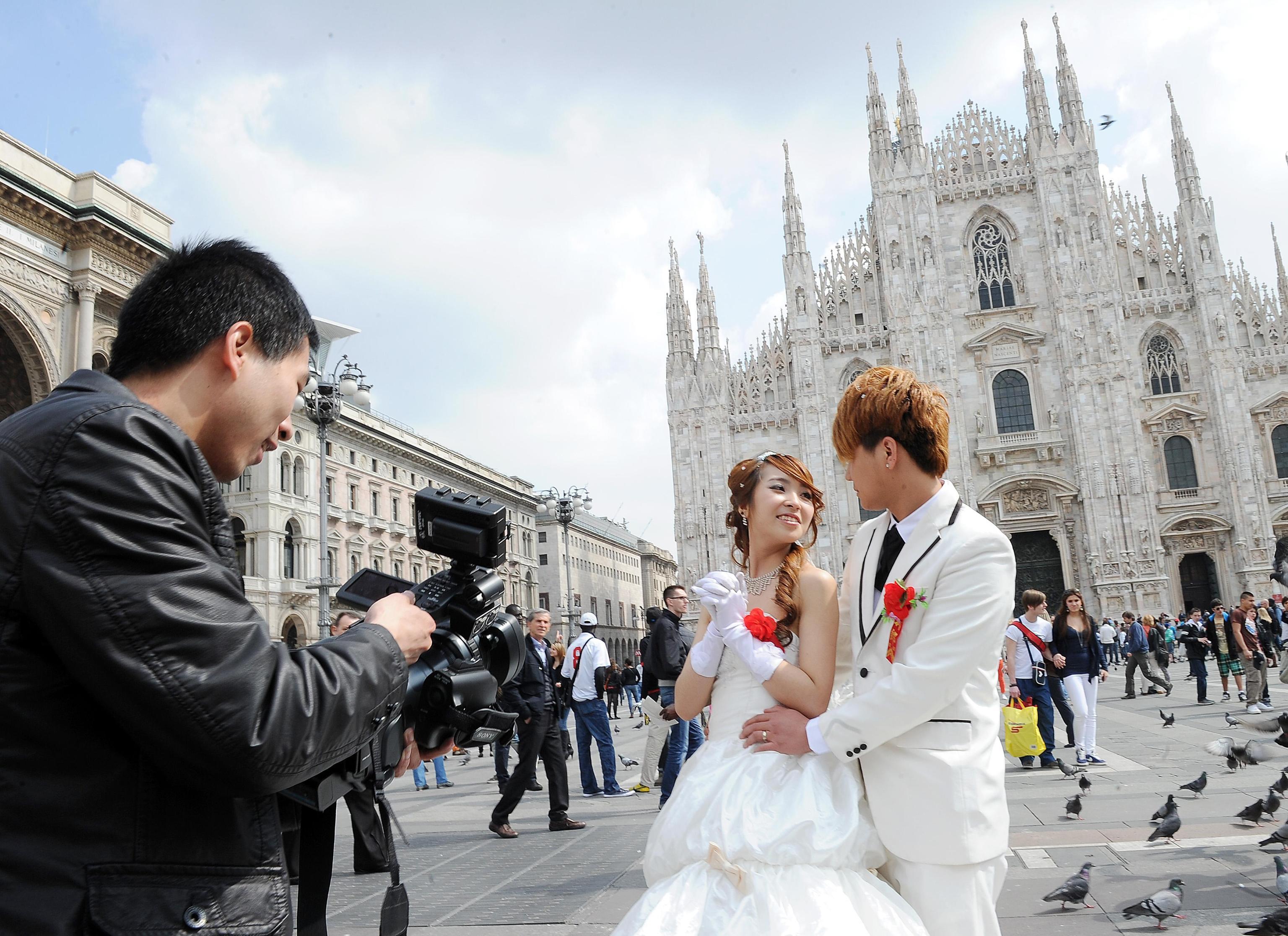Una coppia di neo sposi cinesi approfitta della giornata relativamente soleggiata per una sessione di foto ricordo in piazza Duomo a Milano